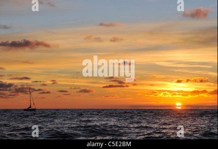 Scenic view of peaceful sea against dramatic sky at sunset - Stock Photo