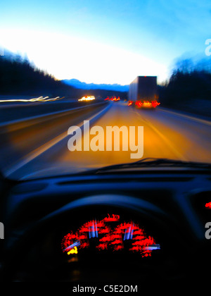 Close-up of dashboard with view of vehicles on the street through windshield - Stock Photo