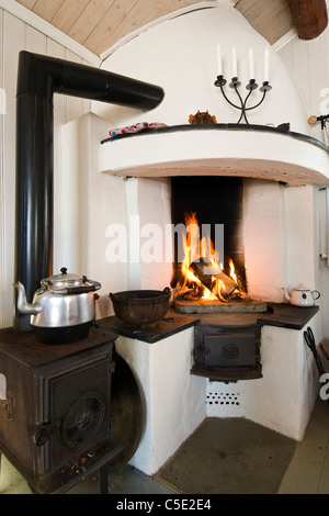 View of kettle by lit fireplace in the house - Stock Photo