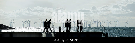 Panoramic shot of silhouette people on jetty by a lake with wind turbines in the background - Stock Photo