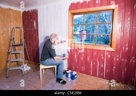 Middle-aged man painting the wooden wall of a house - Stock Photo