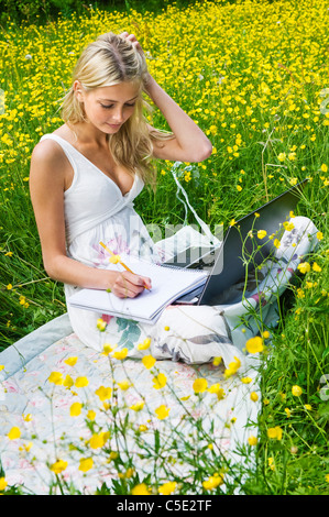 Young woman sitting in a beautiful flowery meadow with a laptop - Stock Photo