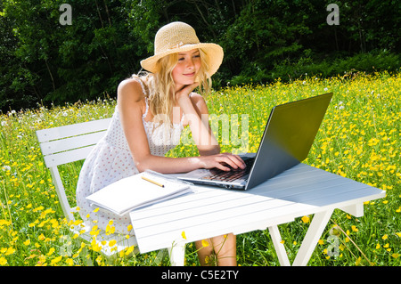 Young woman in sunhat sitting in a beautiful flowery meadow with a laptop - Stock Photo