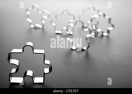 Close-up of Christmas cookie cutters symbolizing jigsaw pieces against gray background - Stock Photo
