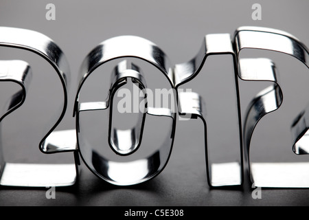 Close-up of Christmas cookie cutters symbolizing 2012 against gray background - Stock Photo