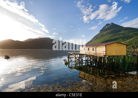 Beautiful view of house by peaceful lake with mountains against blue sky and clouds in Norway - Stock Photo