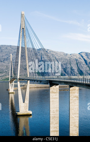 View of Helgeland bridge over the water with mountain range against sky in Norway - Stock Photo