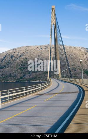 Asphalt road on Helgeland bridge against mountains and blue sky in Norway - Stock Photo