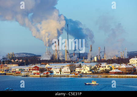Smokes emitting from chimneys with houses and lake in foreground - Stock Photo