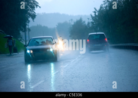 Cars on the asphalt road in rain at dawn - Stock Photo