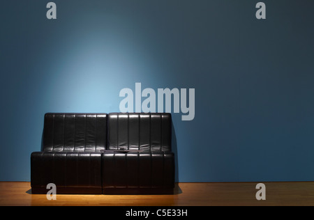 Black leather couch on wooden floor and against blue wall - Stock Photo