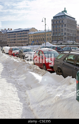 Traffic along the snow with buildings against sky in background at Gothenburg, Sweden - Stock Photo
