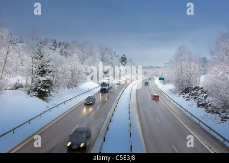 High angle view of blurred vehicles on the country road along snow covered trees - Stock Photo