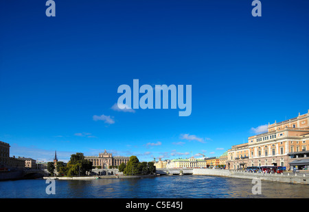 Lake with buildings in the background against the blue sky - Stock Photo