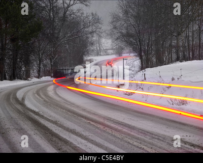 Blurred yellow light trails on snow covered road along trees - Stock Photo