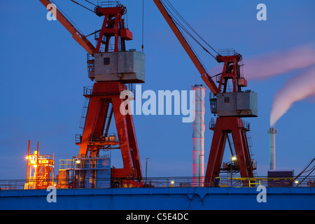 Low angle view of cranes with chimneys emitting smoke against blue sky - Stock Photo