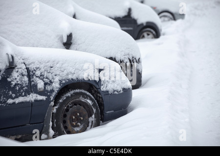 Side shot of snow covered cars in a row - Stock Photo