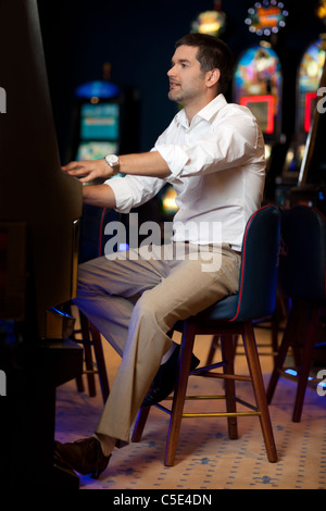 man playing slot machine in a night casino - Stock Photo