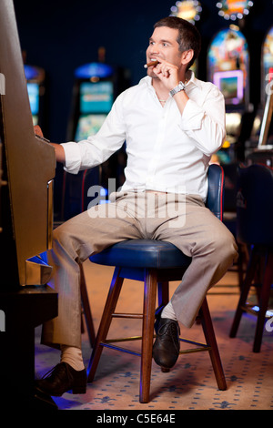 men watching excited the slot machine with cuban cigar in mouth - Stock Photo