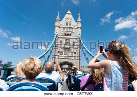 Tourists on open top double decker Original London tour bus crossing Tower Bridge, London, UK - Stock Photo