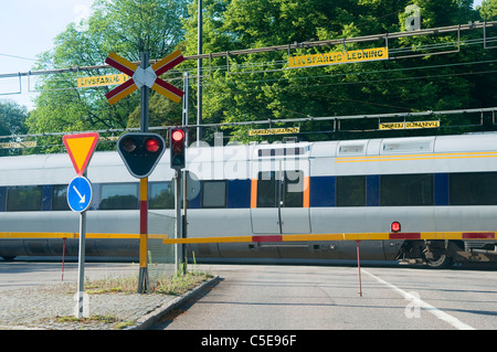 Passenger train passing over railroad crossing with traffic signs in foreground - Stock Photo