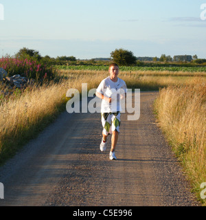 Full length of a teenage boy jogging on dirt country road along the landscape - Stock Photo