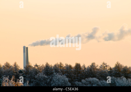 High section of chimney emitting smoke with frosty trees against clear sky at dawn - Stock Photo