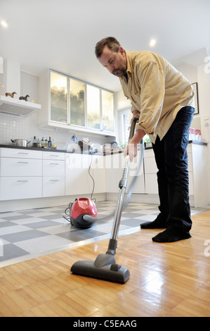 Middle-aged man using vacuum cleaner on the wooden floor with ...