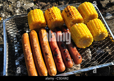 Close-up of sausages and corncobs on the barbecue grill - Stock Photo
