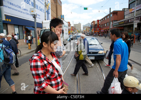 chinese and asian origin people walking across road intersection downtown chinatown toronto ontario canada - Stock Photo
