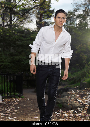 Photo of a stylish young man walking through a park in the evening - Stock Photo