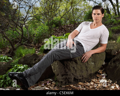 Photo of a stylish young man sitting on a rock in a garden - Stock Photo