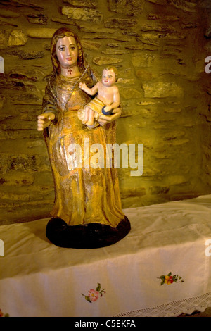 A Virgin Mary holding a Baby Jesus sculpture in a chapel, in Portela de Valcarce, French Way of St. James Way, Galicia, - Stock Photo