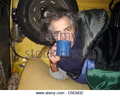 Camping equipment used by explorer Kypros in Africa - mug of tea inside a vehicle while wearing two sleeping bags - Stock Photo