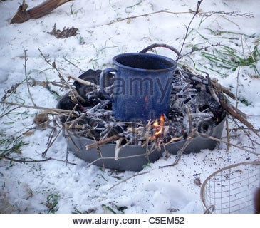Camping equipment used by explorer Kypros in Africa - mug of tea on a camp fire in freezing weather - Spain - Stock Photo