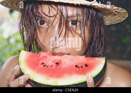 Young woman eating a fresh water melon - Stock Photo