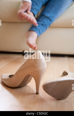 Young woman sat at home rubbing her feet after taking off her high heels - Stock Photo