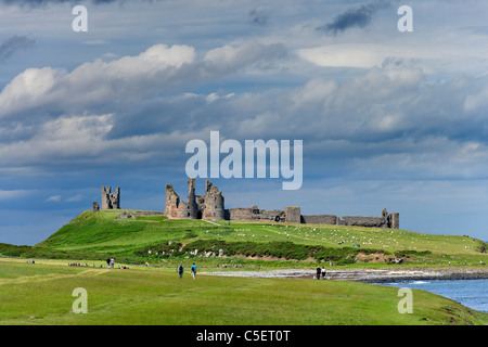 Walkers on the path between Craster and Dunstanburgh Castle on the Northumberland coast, North East England, UK - Stock Photo