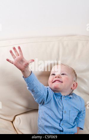 Little cute boy sat on sofa looking up - Stock Photo