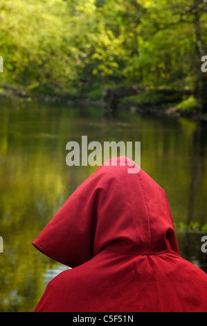 Mysterious person in red cape in the forest by the lake - Stock Photo