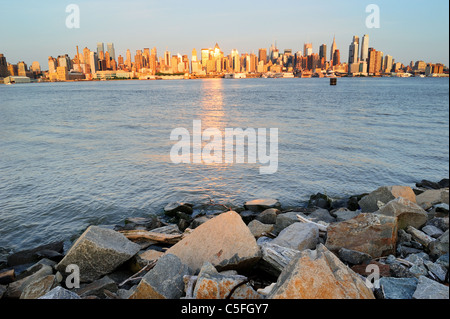 New York City Manhattan midtown skyline at sunset with reflection over skyscraper and river viewed from New Jersey - Stock Photo