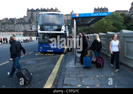 Passenger boarding an Airlink Airport shuttle express bus at a bus stop in the centre of Edinburgh, Scotland UK - Stock Photo