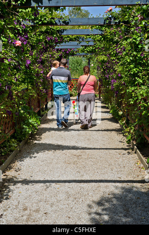 A young family walking along a garden walkway at Paradise Park in Cornwall. - Stock Photo