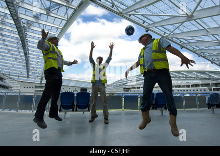 Three builders having a kickabout as work nears completion on the new AMEX stadium, home of Brighton and Hove Albion - Stock Photo
