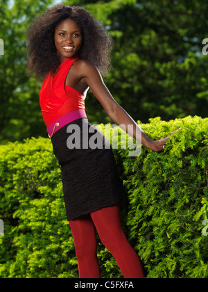 Smiling young stylish black woman in colorful clothes in a park - Stock Photo