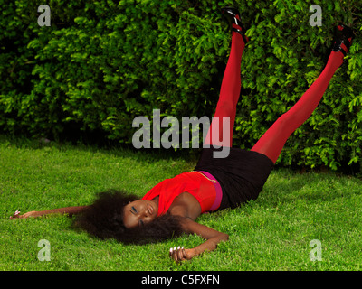 Young stylish black woman in fancy bright clothes lying on the grass in a park - Stock Photo