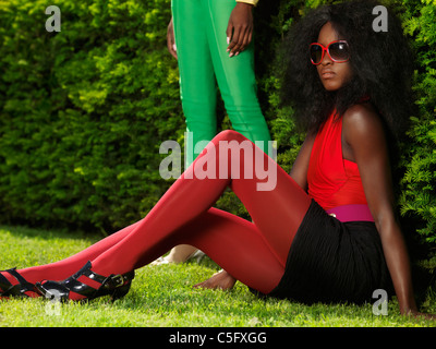 Young stylish black woman in fancy bright clothes sitting on the grass in a park - Stock Photo