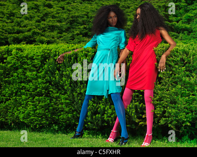 Two beautiful young women wearing bright colorful dressed in a green park - Stock Photo