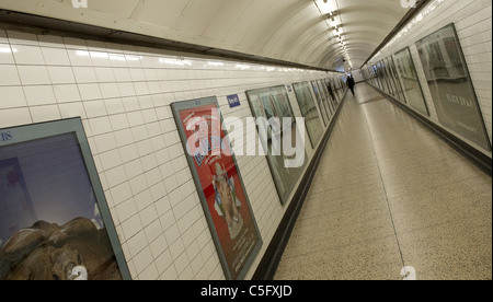 The underground pedestrian tunnel at Charing Cross tube station with one person and adverts for West End Shows and - Stock Photo