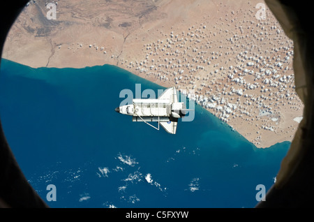 Space shuttle Discovery as seen from the International Space Station above southwestern coast of Morocco March 7 - Stock Photo